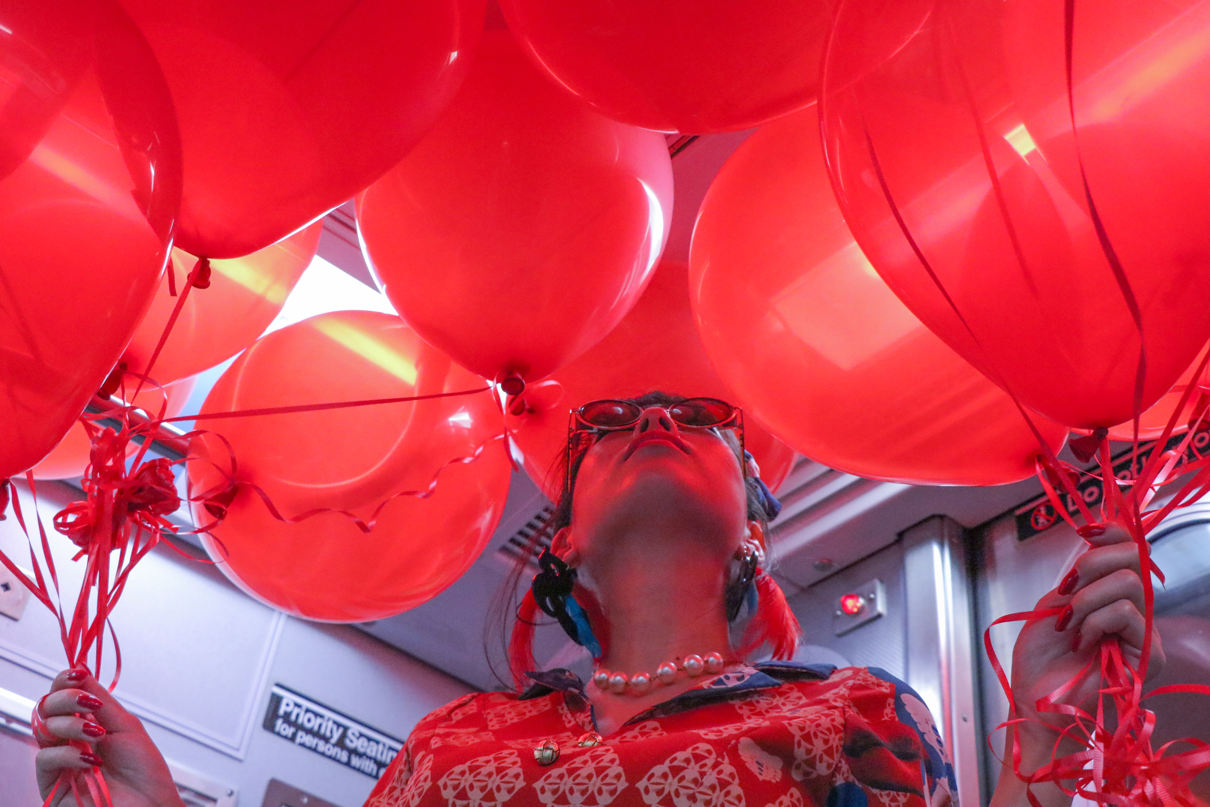 With red balloons in the NY subway